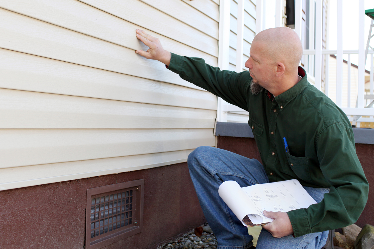 Home inspector checking out aluminum siding on house.