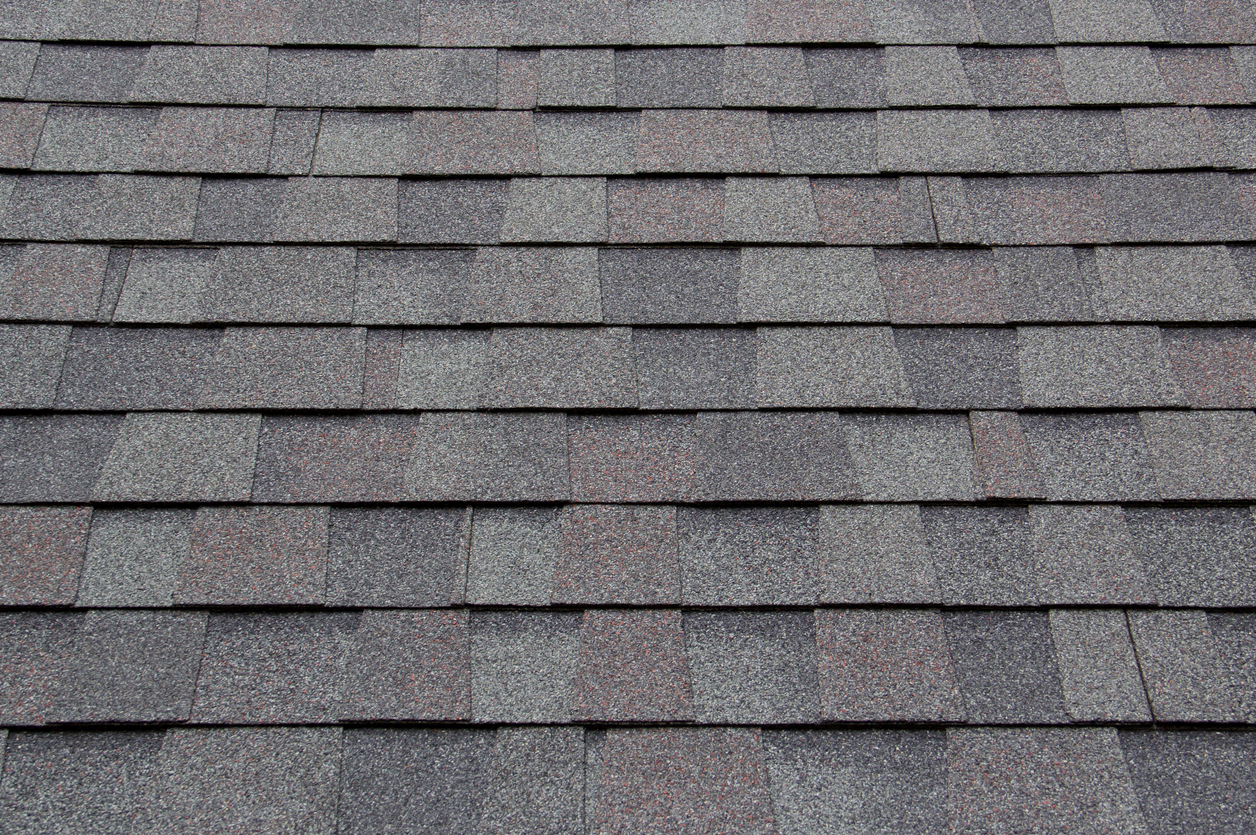 dark new roof shingle background and texture. asphalt tiles of house roof.
